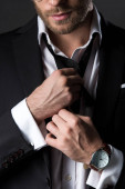 Photo cropped view of man in suit adjusting tie isolated on grey