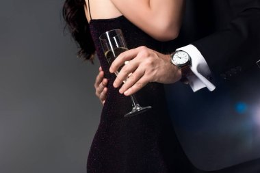 Cropped view of couple hugging and holding glass of champagne on valentines day, isolated on grey stock vector