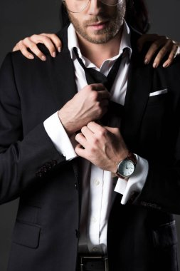 cropped view of woman hugging man in black suit and tie, isolated on grey