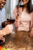 oříznutý pohled na usmívající se multikulturní přátele cinkající sklenicemi na víno v kuchyni