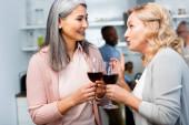 usmívající se žena mluví s asijské přítel a drží víno sklo