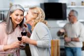 selektivní zaměření usmívající se žena vyzrazení tajemství asijské přítel s vínem sklo