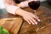 cropped view of woman holding wine glass in kitchen