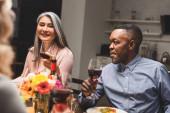 selektivní zaměření usměvavé asijské ženy a africký Američan muž držící sklenice na víno během večeře