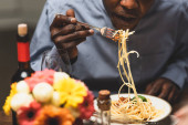 cropped view of african american man eating pasta during dinner