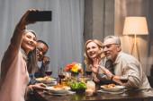 mosolygós multikulturális barátok csinál szelfi okostelefon vacsora közben