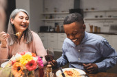 african american man and asain woman smiling during dinner