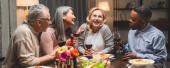 panoráma lövés mosolygós multikulturális barátok beszél, és a kezében boros poharak vacsora közben