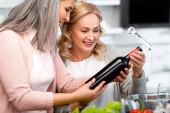 usmívající se multikulturní přátelé při pohledu na láhev vína s vývrtkou v kuchyni