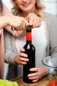 oříznutý pohled na přátele otevření láhev vína s vývrtkou v kuchyni