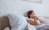 fiatal mosolygós nő álmodik, miközben fekszik az ágyon