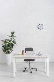 modernes Büro mit Laptop auf Schreibtisch in der Nähe der Ziegelwand