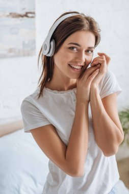 smiling woman looking at camera while listening music at home