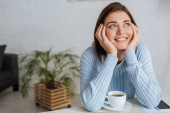 verträumte junge Frau lächelt neben Tasse mit Kaffee
