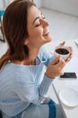 fröhliche junge Frau lächelt, während sie eine Tasse Kaffee hält