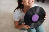 oříznutý pohled na šťastnou ženu držící retro vinylovou desku