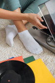 Photo cropped view of girl in white socks touching vinyl record near retro record player