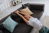 zasněná mladá žena se zavřenýma očima relaxující na pohovce