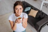 Blick von oben auf eine attraktive Frau, die lächelt, während sie eine Tasse Tee hält