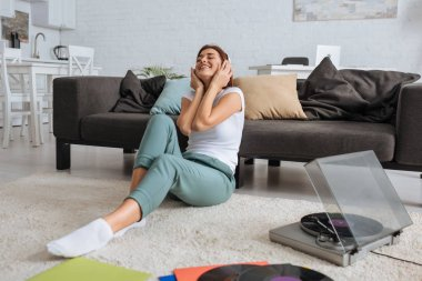 cheerful girl listening music in headphones near vintage record player