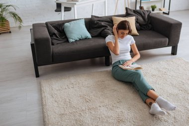 cheerful young woman reading book while chilling near sofa in living room
