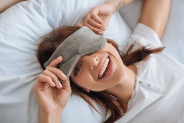 overhead view of happy young woman in eye mask resting in bedroom