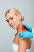 cropped view of doctor in blue latex gloves touching woman neck with red mark isolated on grey