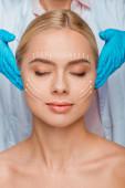 oříznutý pohled na kosmetičku v modrých latexových rukavicích dotýkajících se spánků ženy se zavřenýma očima a plastickými chirurgickými známkami na obličeji