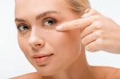schöne Frau zeigt mit dem Finger auf plastische Chirurgie Markierungen unter Augen isoliert auf weiß