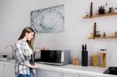 Fényképek oldal kilátás mosolygós nő nézi mikrohullámú sütő a konyhában