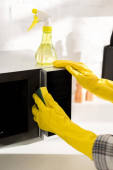 ořezaný pohled na ženu v gumových rukavicích čistící mikrovlnná trouba s houbou