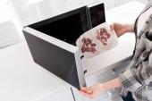 Ausgeschnittene Ansicht einer Frau, die in der Küche Fleisch in die Mikrowelle legt