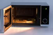kov a otevřená mikrovlnná trouba se světlem na bílém pozadí
