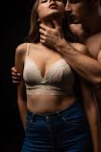 Fotografie Ausgeschnittene Ansicht eines jungen Mannes mit nacktem Oberkörper, der sexy Freundin in BH auf schwarz berührt