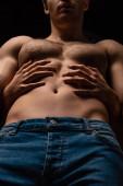 Niedrigwinkel-Ansicht der Frau umarmt sexy jungen Mann mit muskulösem Oberkörper isoliert auf schwarz