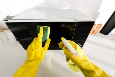 Cropped view of woman in rubber gloves cleaning microwave with sponge stock vector