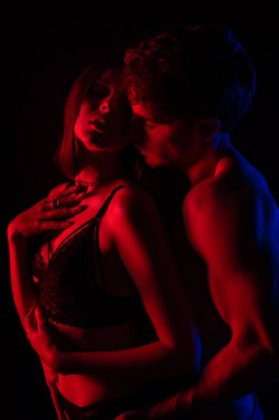 undressed sexy young couple kissing and hugging in red light isolated on black