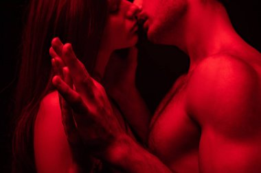 side view of passionate undressed sexy young couple kissing and holding hands in red light isolated on black