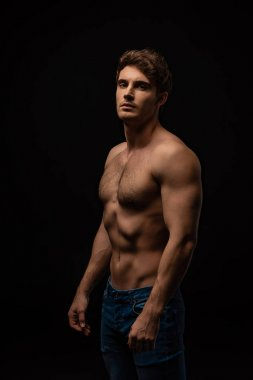 sexy man in jeans with bare muscular torso isolated on black