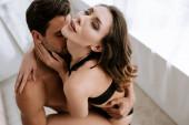 Ansicht von oben: Mann küsst leidenschaftliche Frau in Unterwäsche