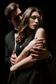 man in suit hugging attractive girlfriend in dress isolated on black