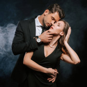 pohledný muž dotýká atraktivní žena v šatech na černé s kouřem