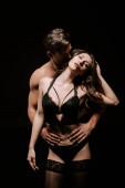 svalnatý muž objímání sexy žena ve spodním prádle a punčochy izolované na černé