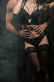 cropped view of passionate man hugging young woman in underwear on black with smoke