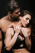 leidenschaftlicher Mann umarmt junge Frau in Unterwäsche isoliert auf schwarz