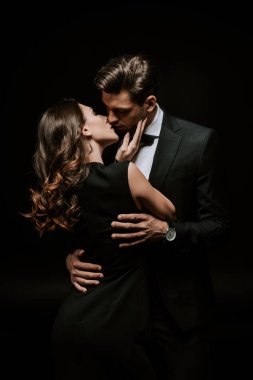 beautiful woman kissing handsome man in suit isolated on black