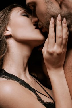 passionate girl with closed eyes kissing handsome man
