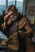 Aufmerksame Schuhmacherin berührt Brille beim Anblick von echtem Leder