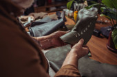 Fotografie Ausgeschnittene Ansicht des Schuhmachers mit Lederdetail des unfertigen Schuhs in der Werkstatt