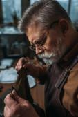 Fotografie Senior, bärtiger Schuhmacher hält Stück echtes Leder in der Werkstatt